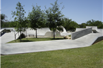 Photo of grassy area with trees in the center of the skate park.